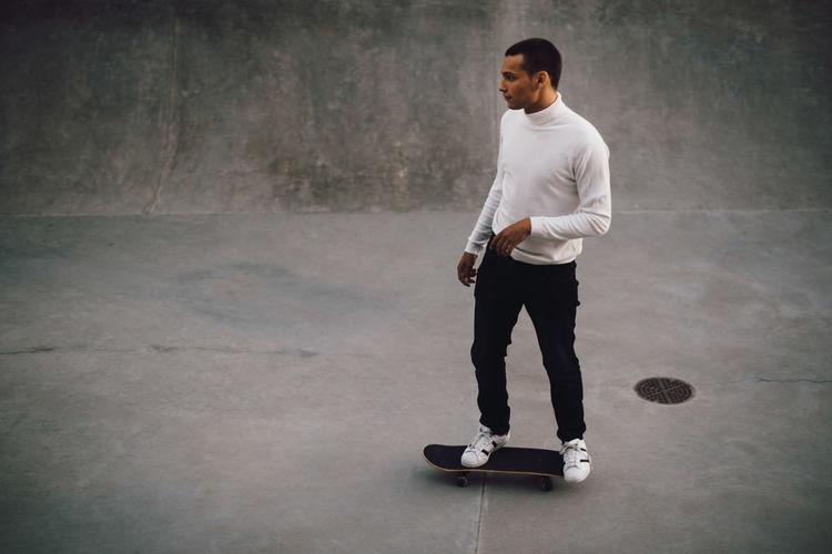 Full length of man standing on skateboard against wall