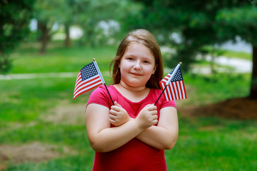 Laughing little girl with long curly blond hair holding american flag and waving it, outdoor portrait on sunny day in Independence Day and Flag Day Holding 4th Of July American American Flag Beautiful Country Dream Freedom Happy Holiday Independence Patriotism USA United States American Culture Beauty Casual Clothing Citizen Citizenship Day Flag Flags Girl Patriotism Smile