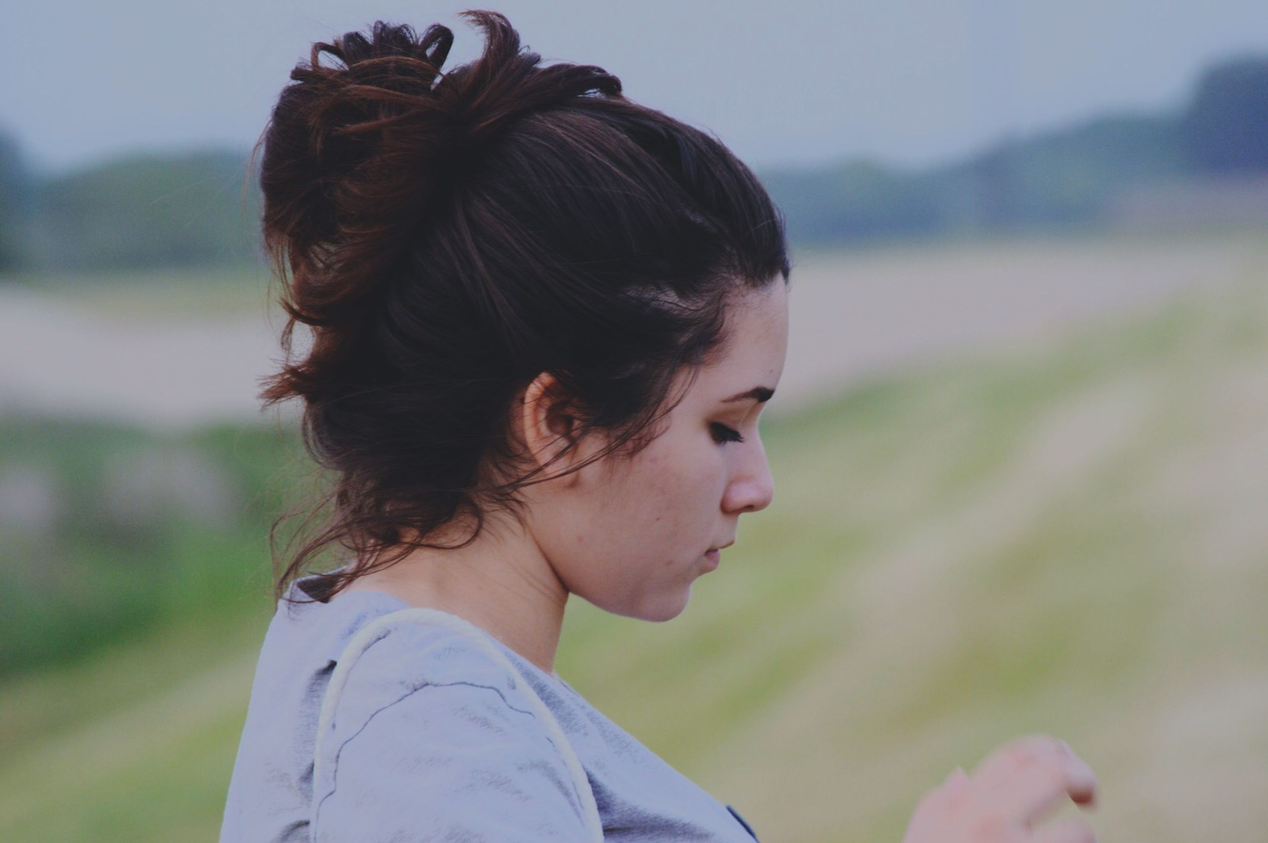 focus on foreground, lifestyles, headshot, leisure activity, long hair, person, young adult, brown hair, young women, casual clothing, close-up, waist up, rear view, head and shoulders, side view, blond hair, outdoors, looking away