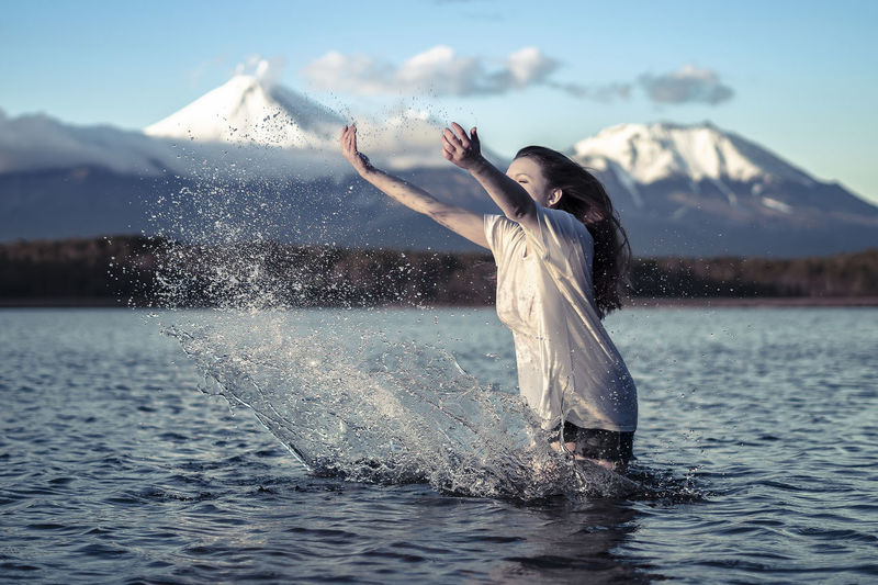 Young woman splashing water while standing in lake against snowcapped mountain