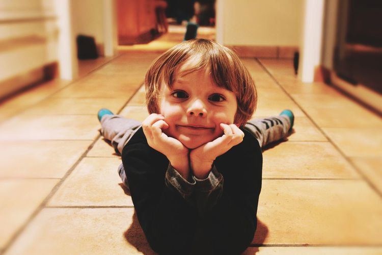 Portrait Of Cute Boy Lying On Floor At Home