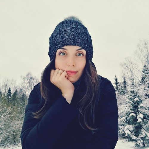 Portrait of young woman in warm clothing against sky
