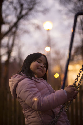 Belgrade Bokeh Cheerful Day Focus On Foreground Girl Happiness Holding Illuminated Night One Person One Young Woman Only Outdoors Park People Playing Real People Sky Smiling Swing Tree Warm Clothing Winter Young Adult