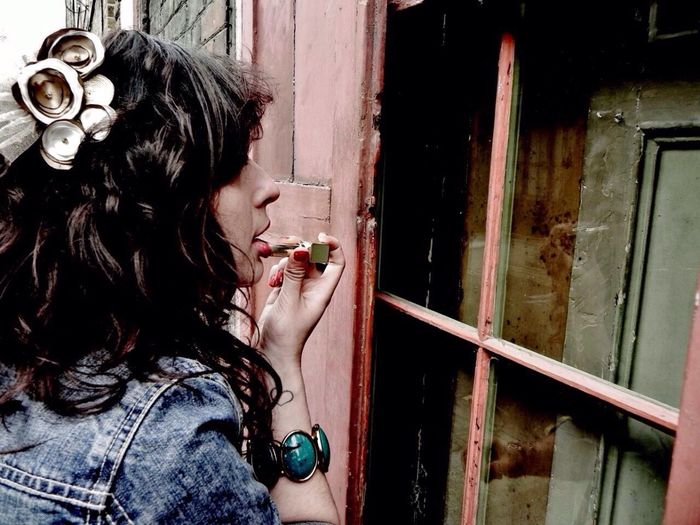 Side view of young woman applying lipstick outside old house