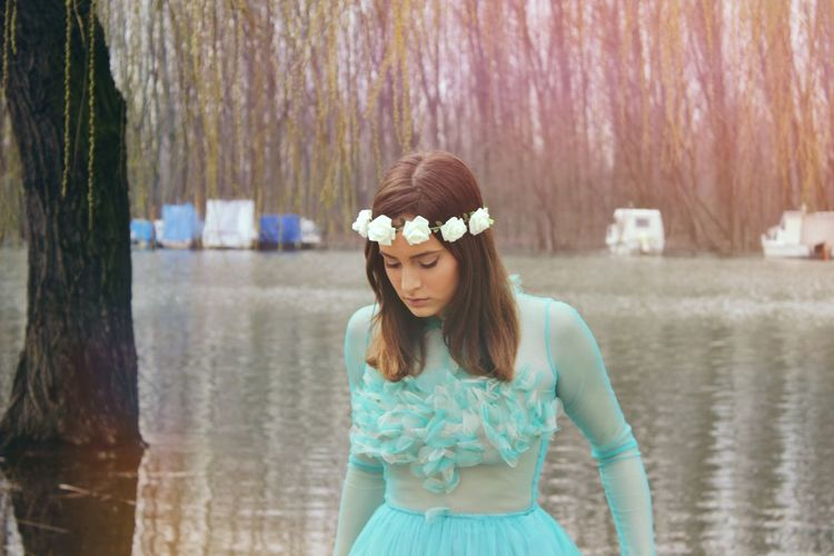 Young woman in turquoise dress looking down against lake