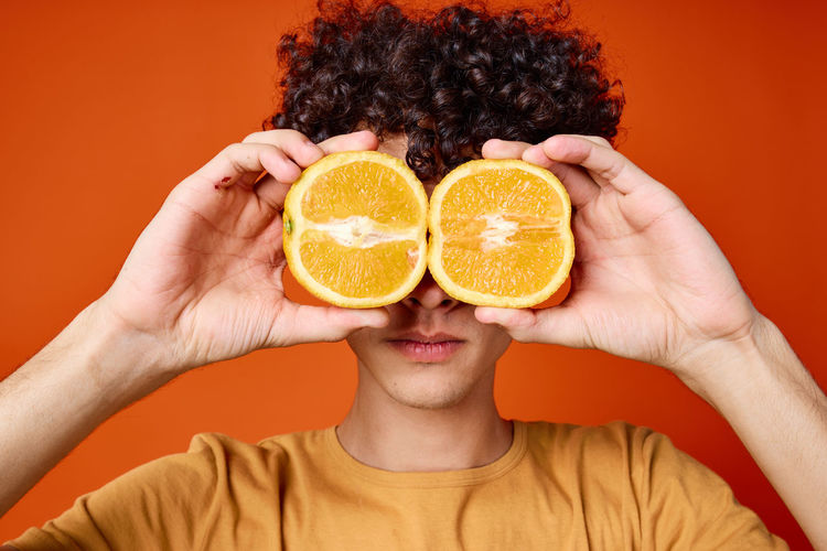 Portrait of woman with orange fruit against gray background