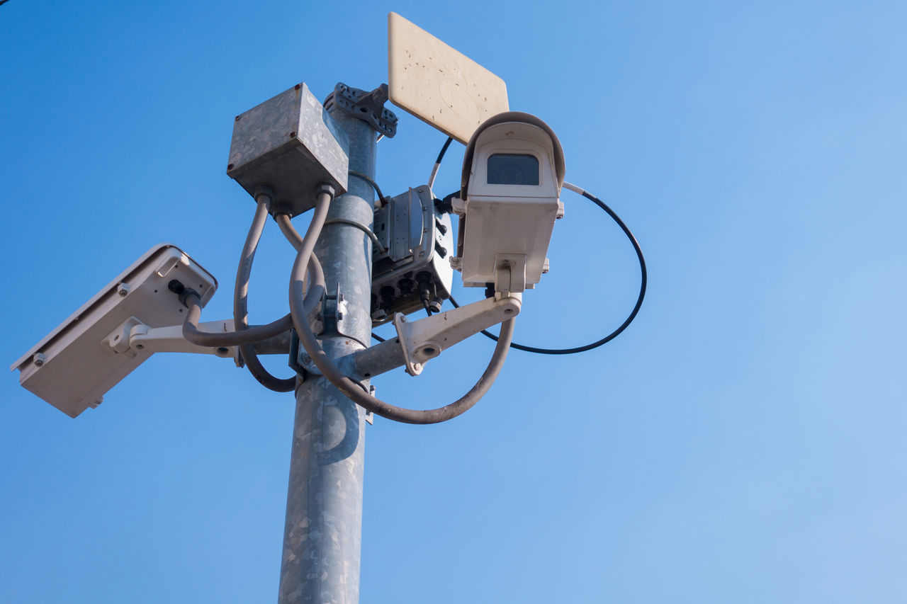 low angle view, sky, blue, technology, clear sky, nature, day, metal, security camera, no people, electricity, sunlight, surveillance, outdoors, fuel and power generation, lighting equipment, pole, communication, security, copy space, power supply, electrical equipment
