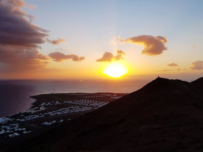 Volcano in Lanzarote, Canary Islands Town Mountain Ocean Sea SPAIN Canary Islands Lanzarote Volcano Sunset Beautiful Sky Sunset Beauty In Nature Scenics - Nature Sea Land Water Beach Tranquility Nature Cloud - Sky Horizon Over Water Idyllic Non-urban Scene Horizon Sun Sunlight Outdoors