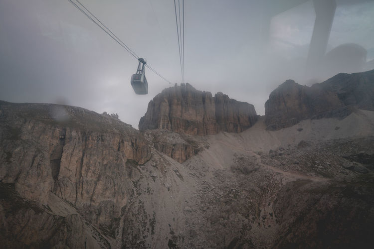 Overhead cable car in mountains against sky