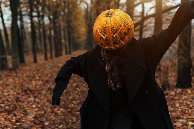 Woman wearing jack o lantern while standing in forest during autumn