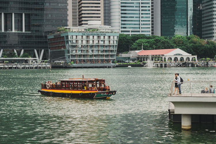 People sailing on river by buildings in city