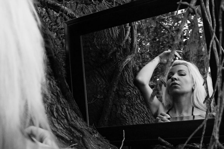 Low angle view of woman reflecting in mirror on tree
