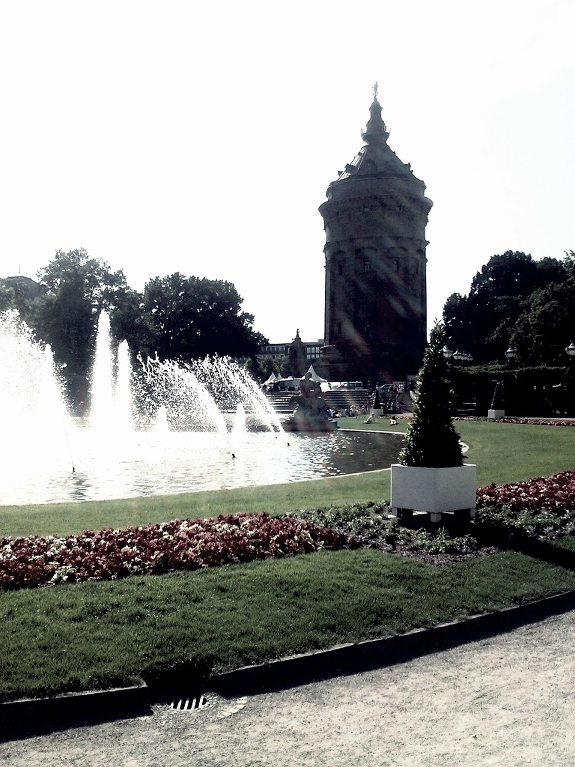 water, fountain, built structure, tree, architecture, building exterior, clear sky, travel destinations, grass, sky, pond, park - man made space, nature, famous place, plant, tourism, spraying, beauty in nature, growth, incidental people