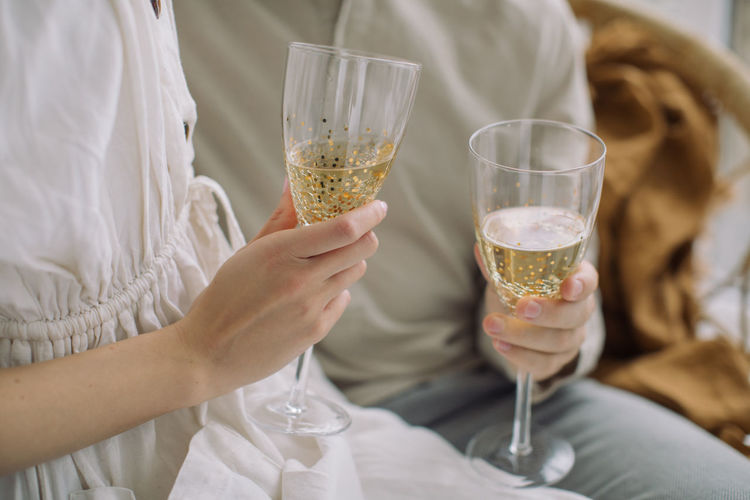 Midsection of couple holding champagne flutes while sitting at home