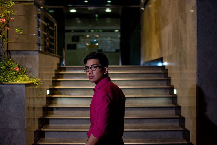 Portrait Of Young Man Standing Against Building At Night