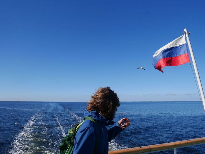 Russia Patriotic Looking At View Hairstyle Outdoors Horizon Over Water Wind Horizon Scenics - Nature Flag Beauty In Nature Day Leisure Activity One Person Lifestyles Blue Nature Copy Space Rear View Clear Sky Real People Sea Sky Water