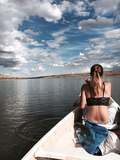 Rear view of sensuous woman sitting in boat over river against sky