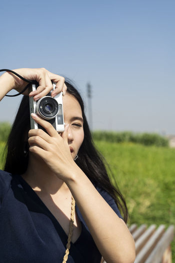 Portrait of woman photographing against sky