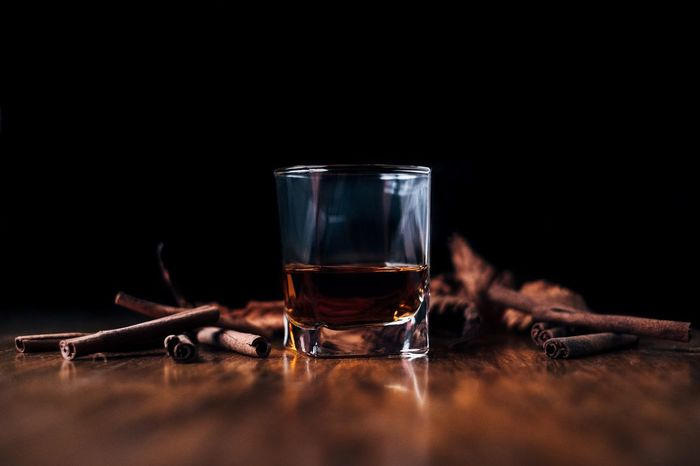 a glass of whiskey and cinnamon sticks Food And Drink Drink Drinking Glass Shot Glass Alcohol Table Selective Focus Refreshment Wood - Material No People Whiskey Black Background Tequila - Drink Freshness Liqueur Cinnamon Cinnamonrolls Beverages Copy Space Drinks Wooden Table Bar Leaves Autumn Background