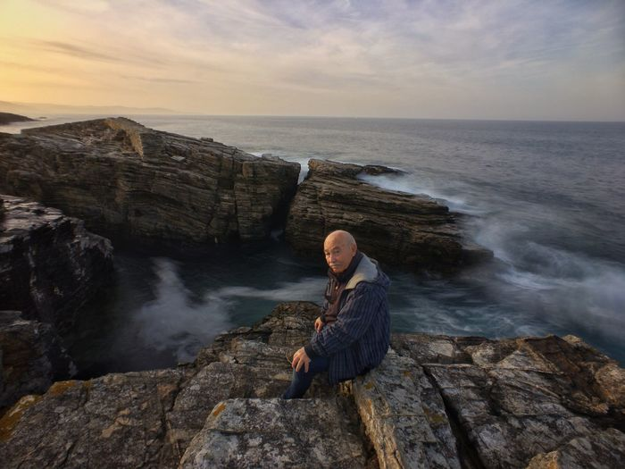 Portrait of senior man sitting on rock by sea against sky during sunset