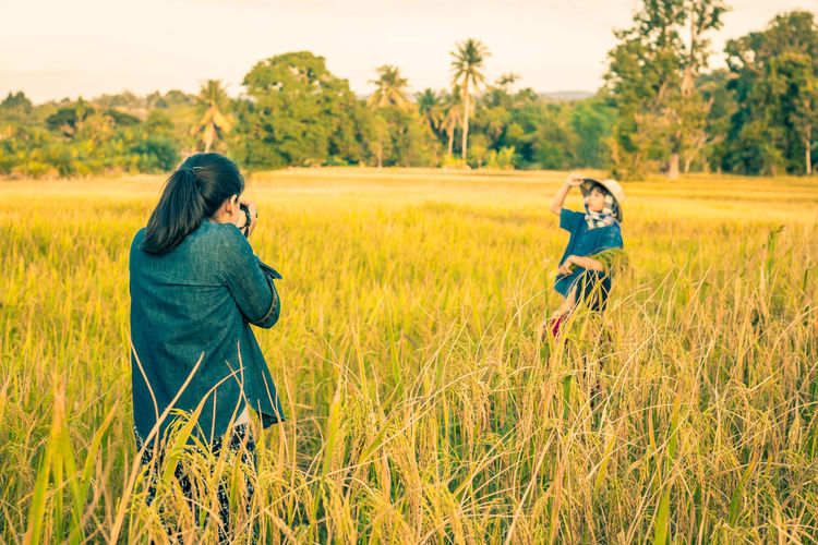 Rear View Of Woman Photographing Girl Standing Amidst Plants On Field