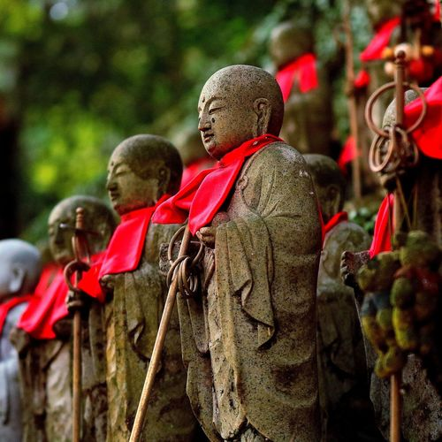 Sculptures of buddha in row outdoors