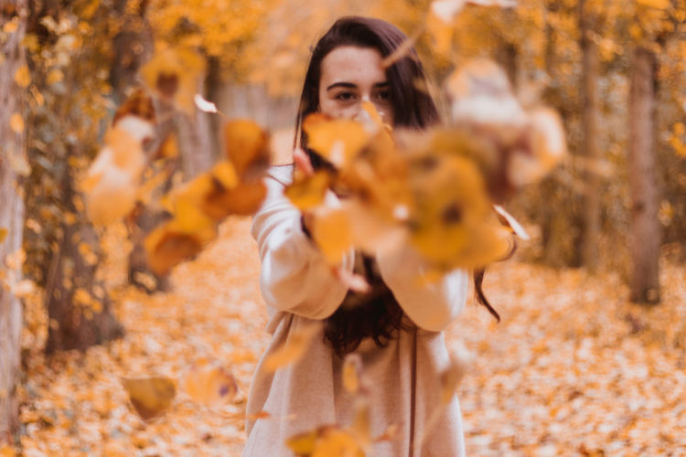 Portrait of young woman playing with autumn leaves