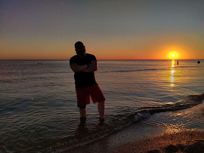 Full length of man standing on beach during sunset