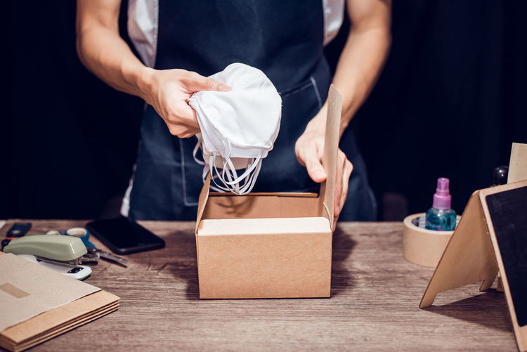 Midsection of woman packing masks in box on table