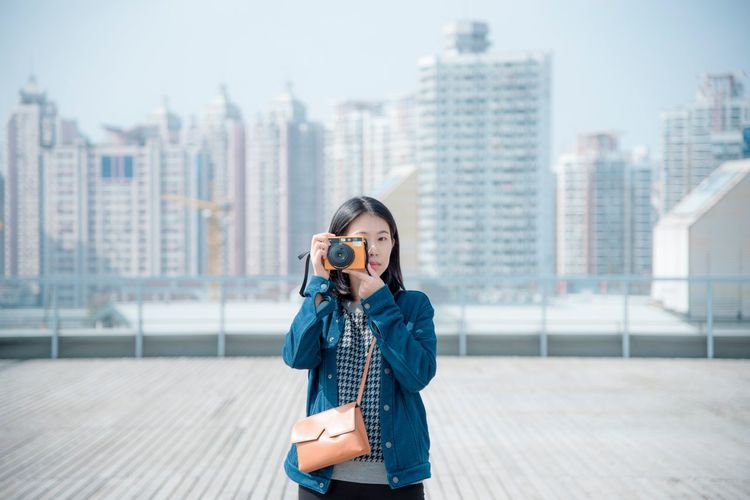Portrait Of Young Woman Photographing Against City