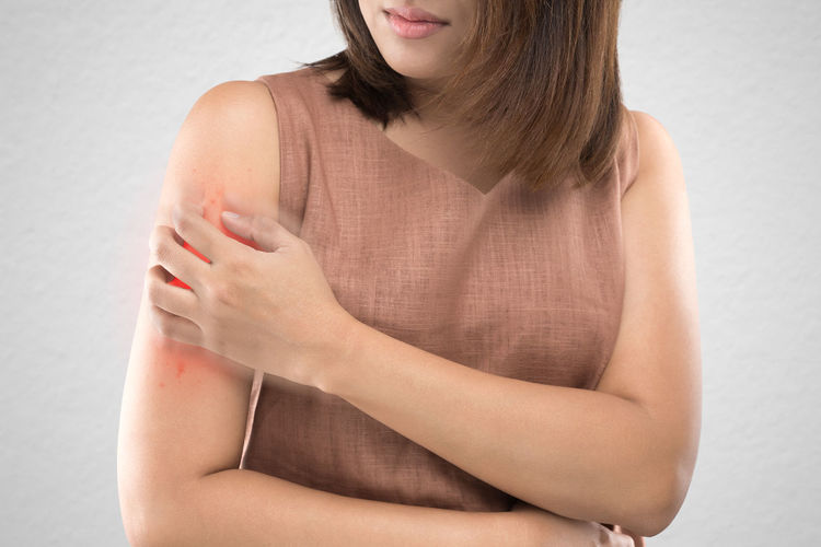Midsection of mid adult woman with wounded hand while standing against wall