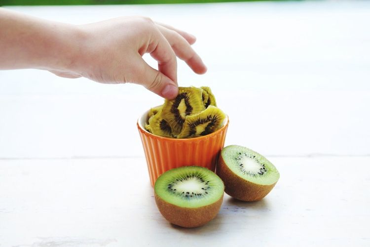 Cropped Image Of Hand Holding Kiwi Slice On Table