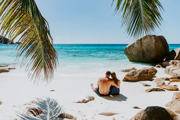 couple relax on beach in tropics. Honeymoon couple travel in tropics in hot summer Couple Travel Vacations Honeymoon Togetherness Love Beach Tropical Exotic Sand Beach Resort Luxury Luxury Hotel Authentic Moments Walking Maldives Seychelles Island Ocean Exploring Adult Adventure EyeEm Best Shots Leisure Activity