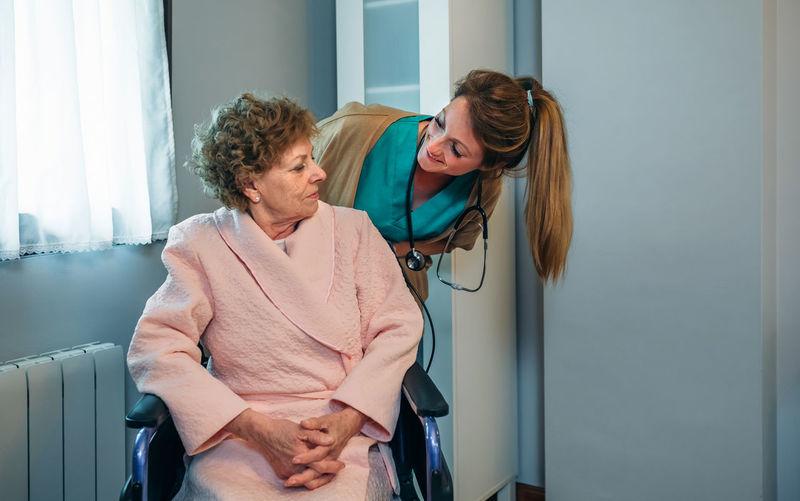 Nurse With Senior Patient On Wheelchair In Hospital Ward