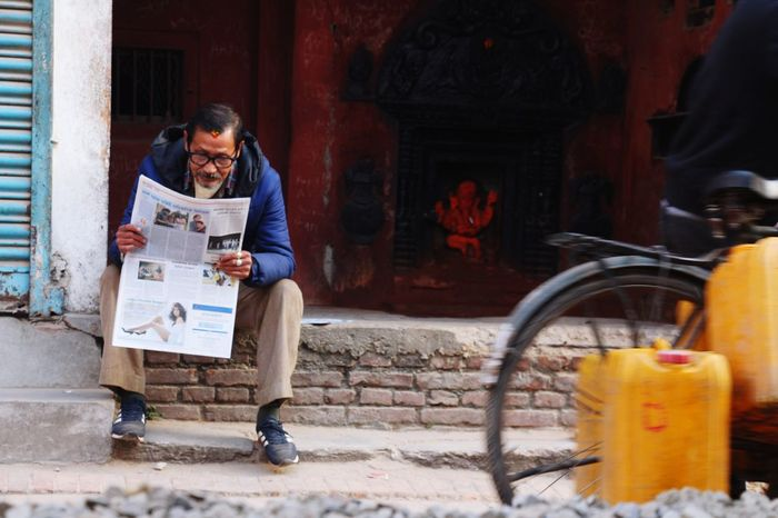 reading on street. One Person Adult Composition Streetphotography Eyeemnepal Reading Reading On The Street Readingonstreets City Life Temple Culture