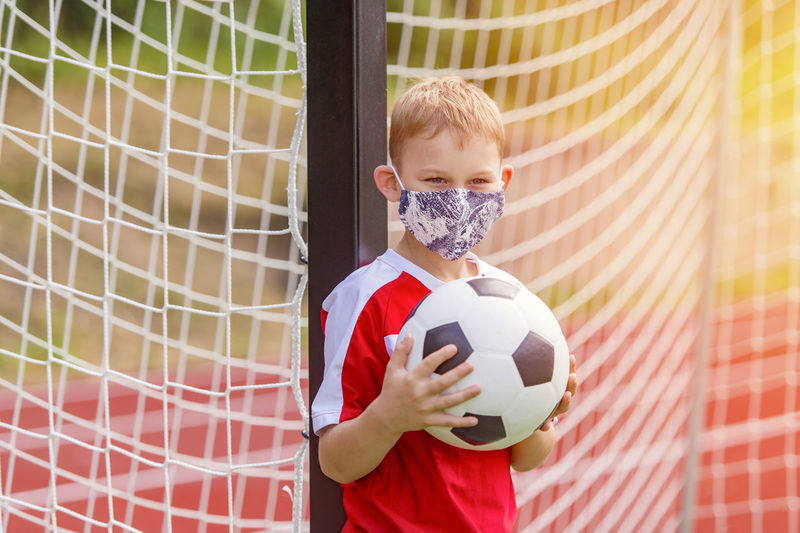 Portrait of boy wearing mask holding soccer ball standing by net