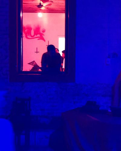 Silhouette man and woman sitting on illuminated window