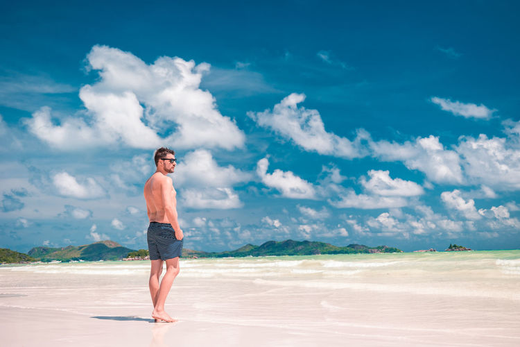 Vacation Sky Holliday Seychellen White Beach Seychelles White Tropical Ocean Praslin Man EyeEm Selects Sea Beach Men Full Length Water Sand Summer Portrait Blue Shirtless Swimming Trunks Surfing Swimming Cap Surfer Paddleboarding Aquatic Sport Surf Wave