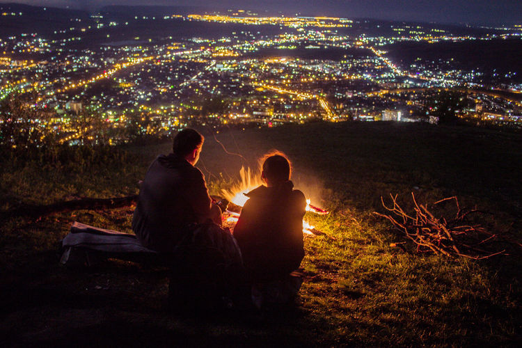 Rear view of couple sitting by bonfire at night