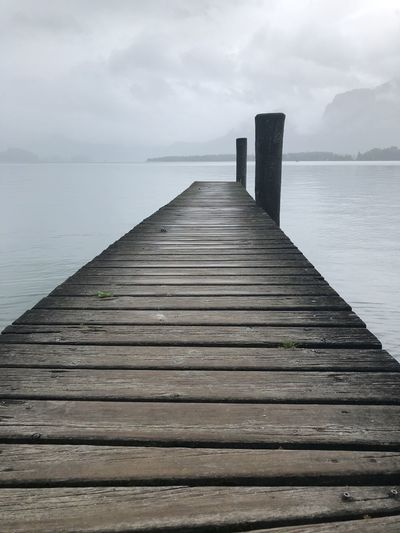 Surface level of wooden pier over sea against sky