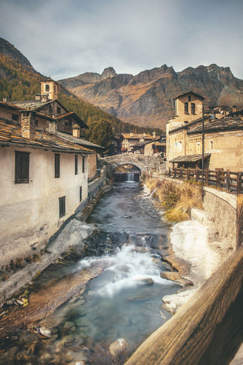 View of river flowing amidst building against mountain