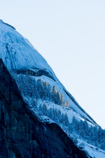 Low angle view of icicles on mountain against clear sky