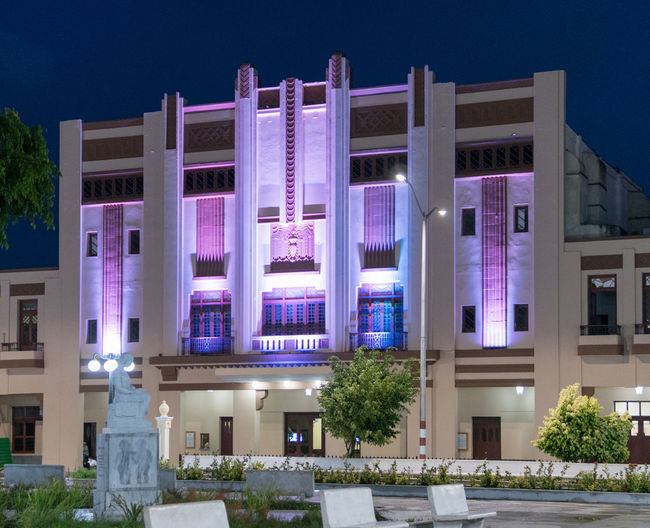 Holguin, Cuba - August 31, 2017: The Teatro Eddy Suñol building located in Calixto García Park illuminated with blue light in the evening. Attraction Calixto Garcia Caribbean Cuba Cuban Culture Travel Historic Latin America Park Parque  Theatre Teatro Eddy Sunol Tourism Holguin Hangout Benches Nightlife Statue