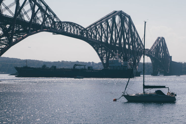 Low angle view of cantilever bridge over river against clear sky