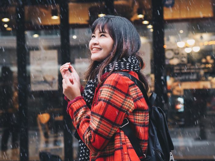 Smiling woman standing in city during winter