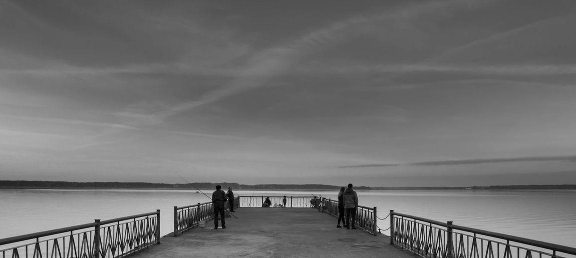 People on pier in lake against sky