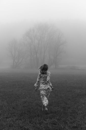 Rear view of woman on field during foggy weather