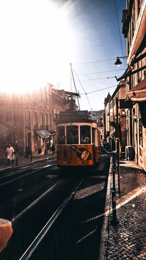 Architecture Building Exterior Built Structure Cable Car City Day Incidental People Land Vehicle Lisboa Mode Of Transportation Nature Outdoors Public Transportation Rail Transportation Railroad Car Railroad Track Sky Street Sunlight Track Train Train - Vehicle Transportation