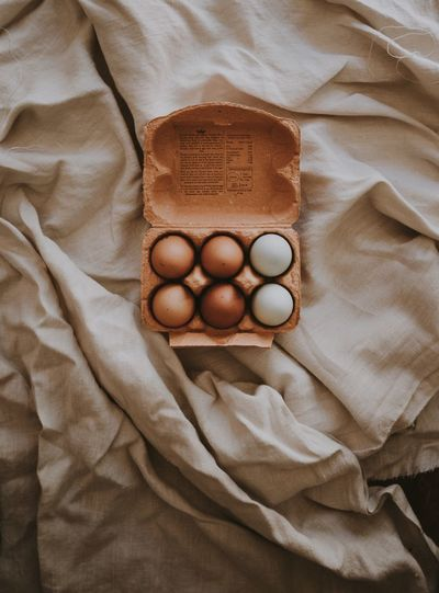 Box of eggs Indoors  High Angle View Directly Above Bed Food Brown No People Food And Drink Egg Still Life Textile Freshness Wellbeing Healthy Eating Sheet Furniture Linen Raw Food Close-up Healthcare And Medicine Breakfast