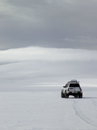 Car on snow covered landscape against sky